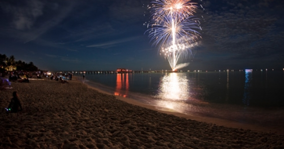 Firework show on the ocean water by the sand