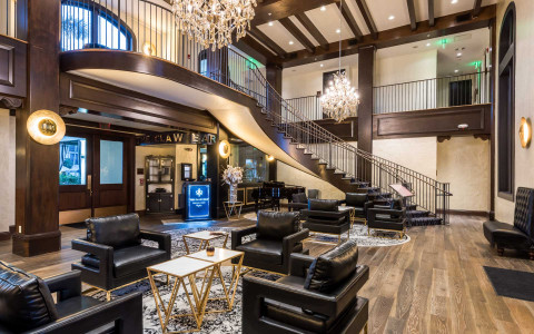 luxurious open concept hotel lobby with staircase, chandeliers, chairs and tables
