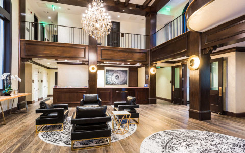 luxurious open concept hotel lobby with front desk, chandelier, leather chairs and black and white area rugs