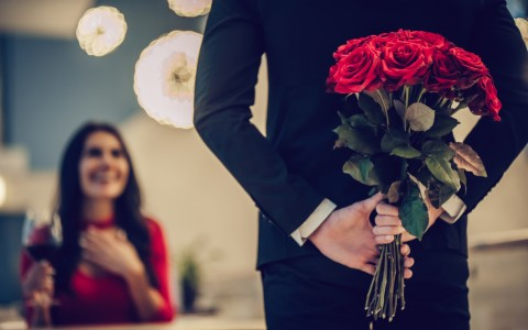 man surprises date with red rose bouquet