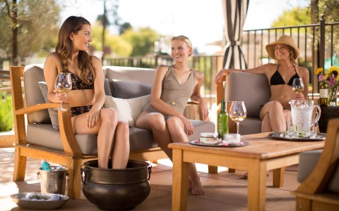 Three women sitting in gray cushioned chairs drinking wine