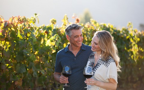Man and woman walking through vineyard with a glass of wine in hand