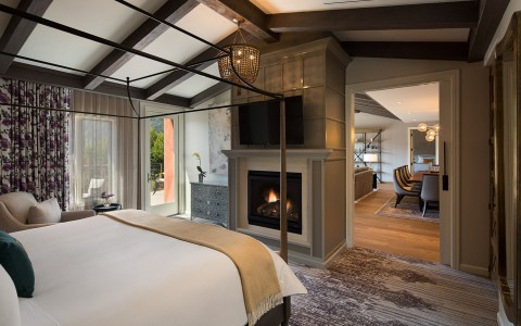 White four poster bed in front of fireplace