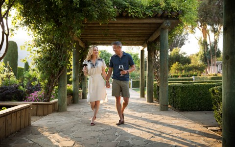 Man and woman walking under a pergola with wine glasses in hand