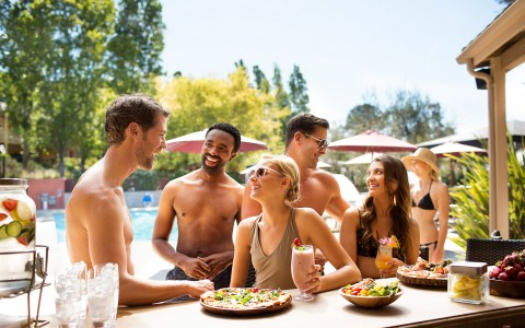 Group of people sitting by pool eating and drinking