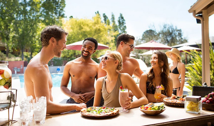 friends standing around a pool bar with drinks and food