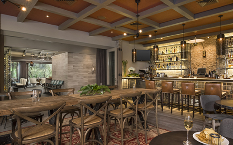 Rustic indoor dining space with wooden tables & chairs next to bar stocked with liquor event