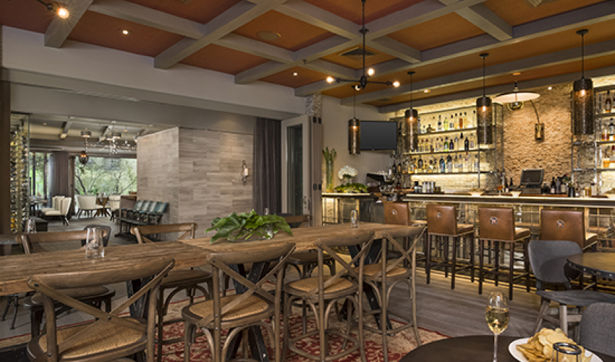 Rustic indoor dining space with wooden tables & chairs next to bar stocked with liquor