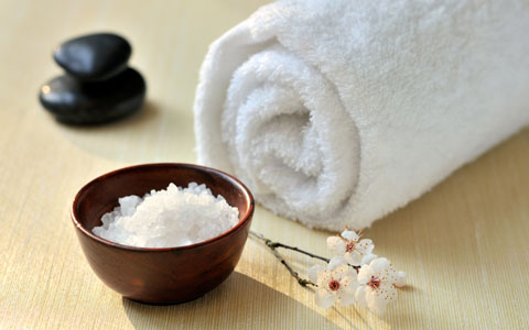 rolled towel next to a bowl of salt and massage stones