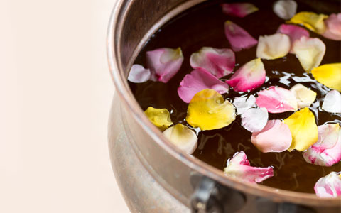 bowl filled with water and rose petals