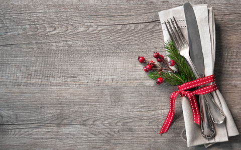 Silverware wrapped on napkin with holly berries & red ribbon  event