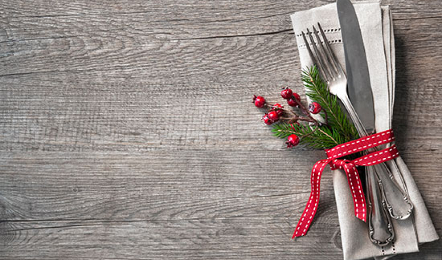 Silverware wrapped on napkin with holly berries & red ribbon