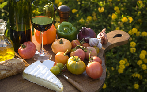 wooden cutting board full of fresh vegetables brie and wine event