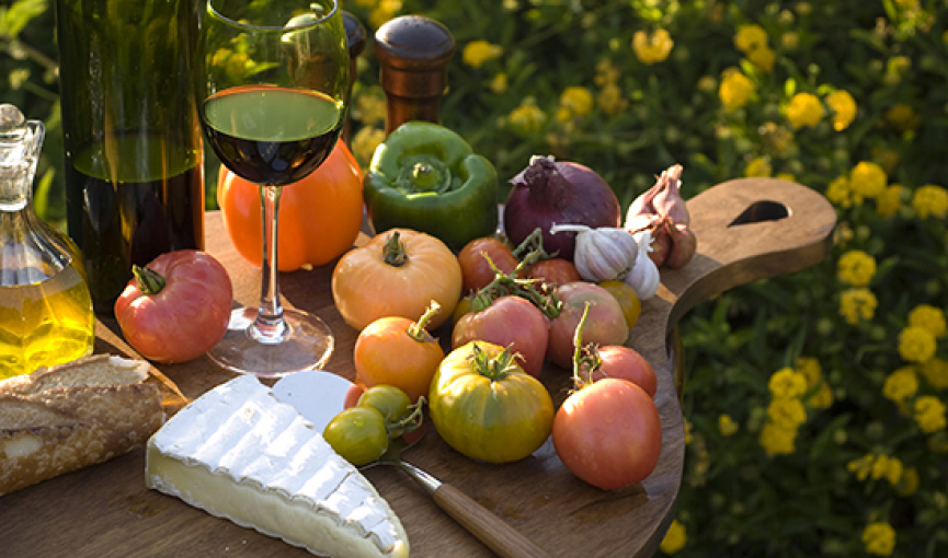 wooden cutting board full of fresh vegetables brie and wine