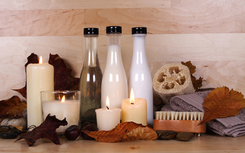 Lit up candles next to bottles of salts & other spa essentials event