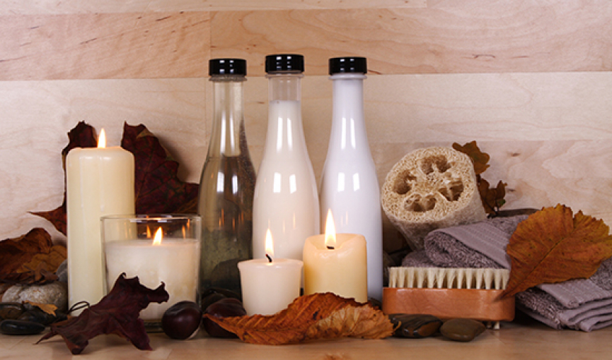 Lit up candles next to bottles of salts & other spa essentials