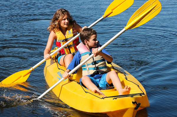 Girl & boy kayaking with yellow vests on