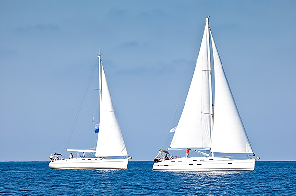 Two white sailboats on ocean
