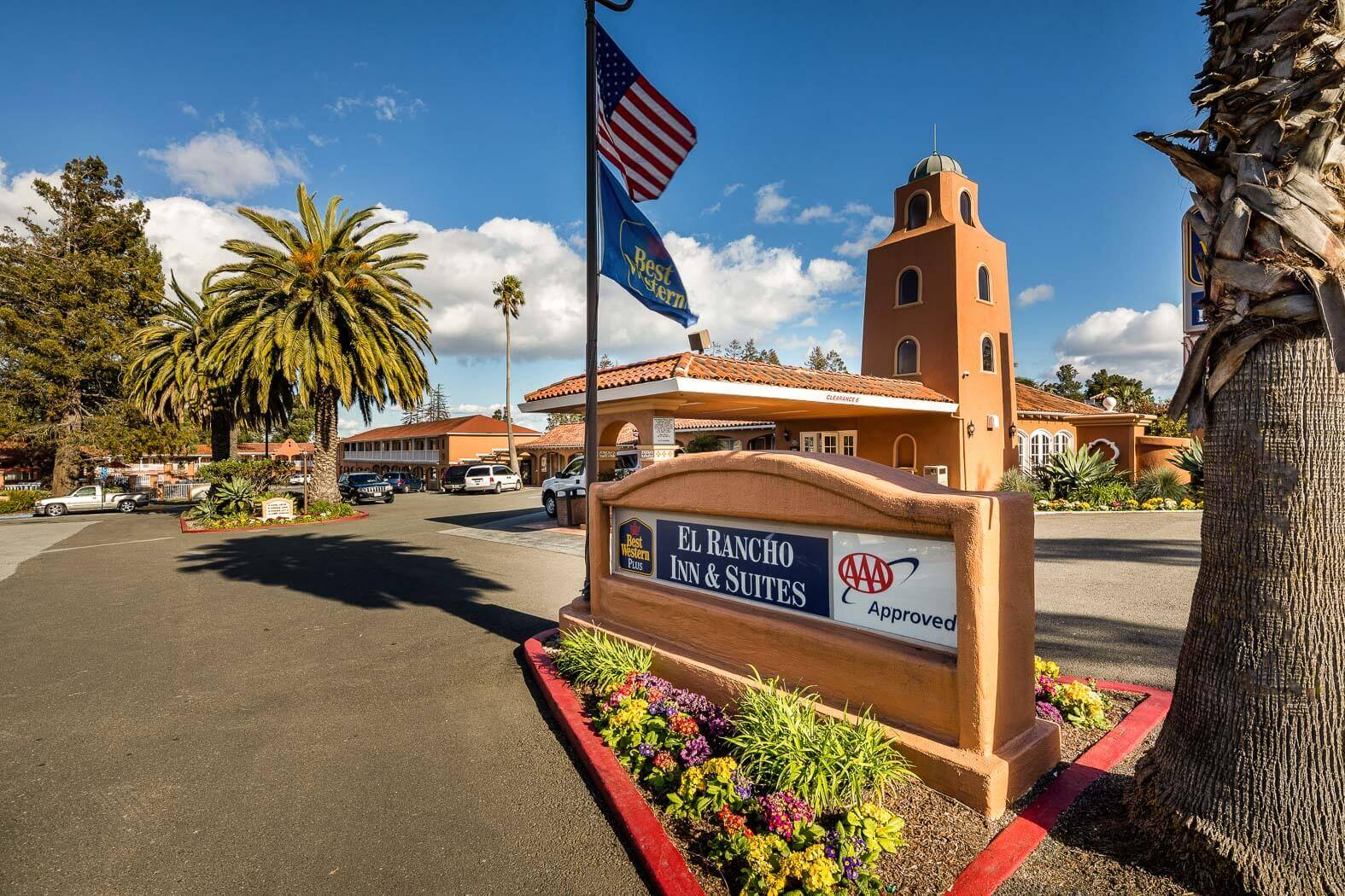 Street and entrance sign to El Rancho Inn & Suites with hotel in the background