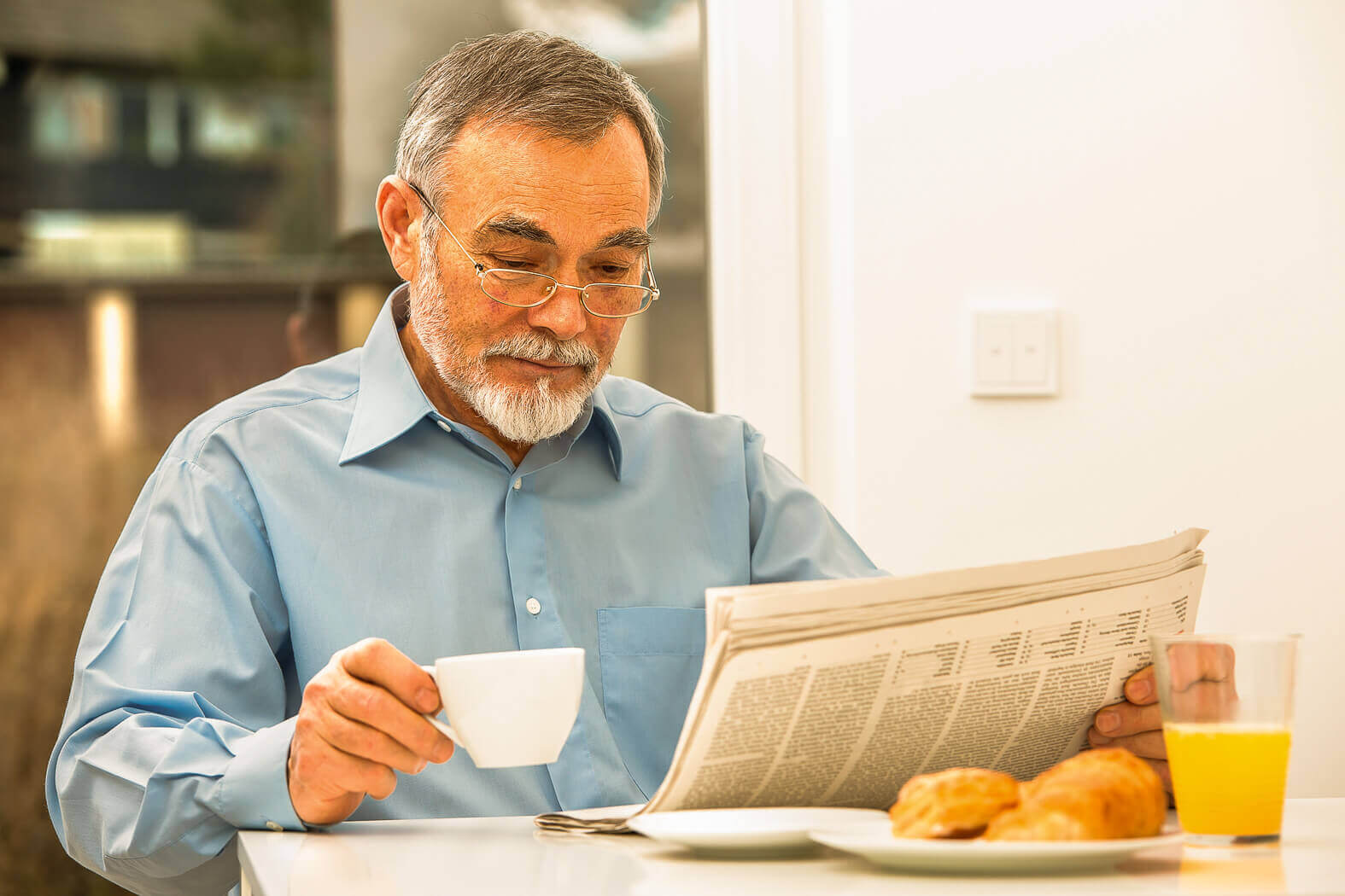 Mature man reading the paper and enjoying a cup of coffee, orange juice and a plate of croissants.
