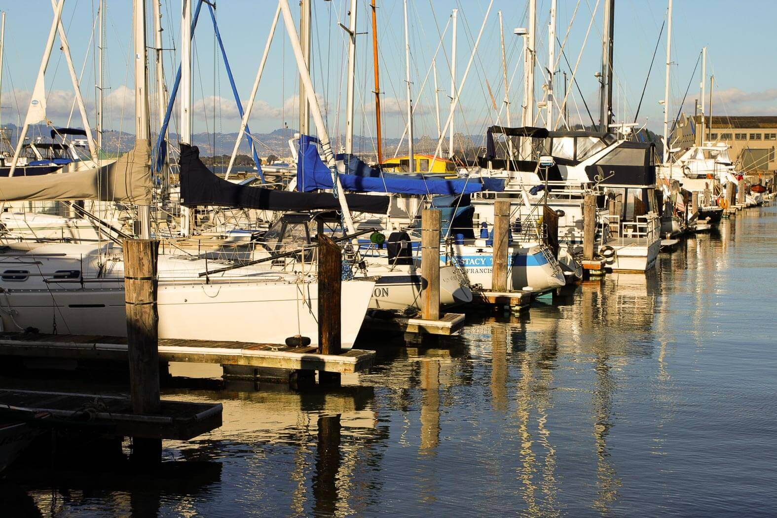 A marina with docked sailboats and calm water