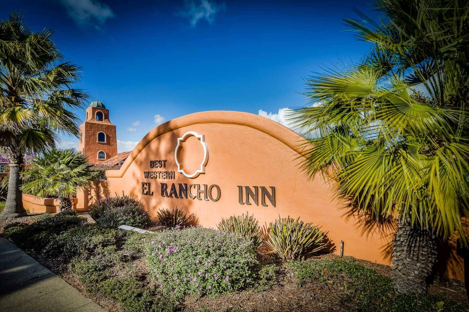Entrance sign to the Best Western Plus El Rancho Inn surrounded by palm trees and shrubbery