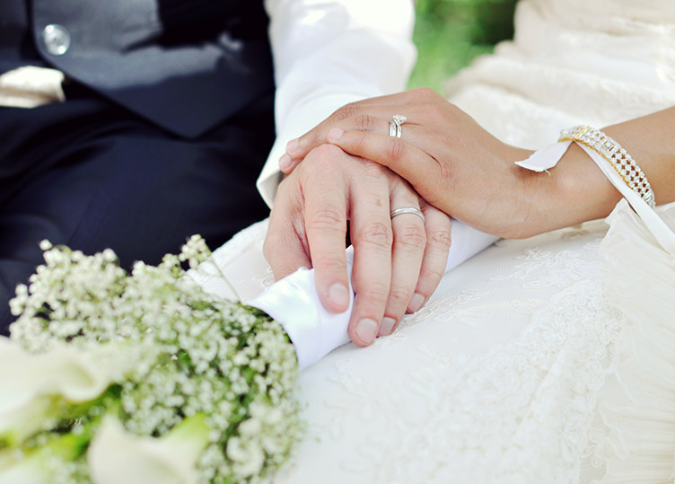 a man in a suit holding hands with a woman in a wedding dress