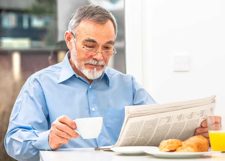 Gentleman reading the newspaper holding coffee cup