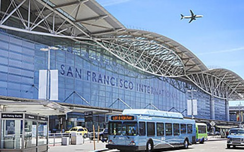 San Francisco International Airport with an airplane above it in the sky and blue busses outfront
