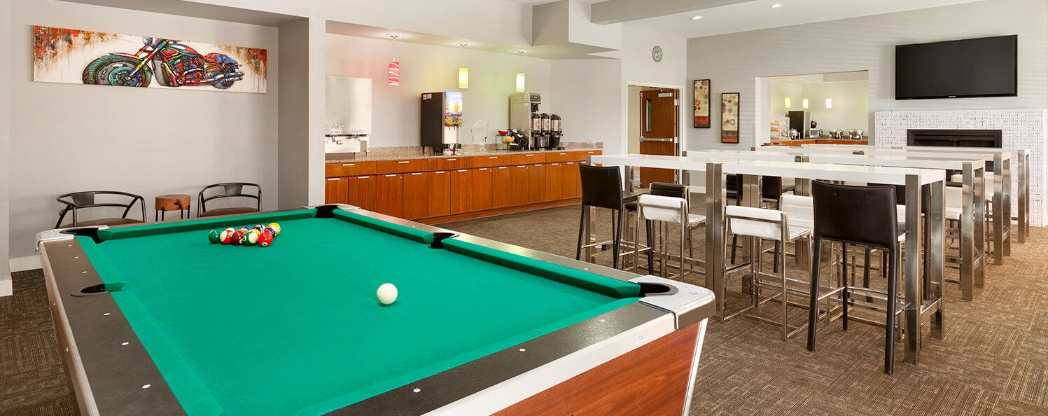 Our hospitality room featuring a billiards table, TV and relaxation area.