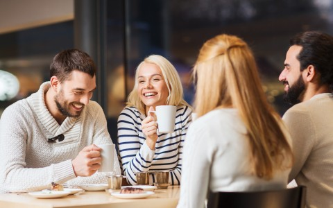 2 Men and 2 Women Sitting at a Table having Coffee and Pastries