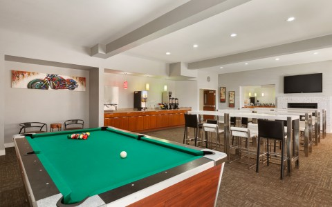 Pool Table, Chairs at Tables Facing Flat Screen TV in Recreation Room