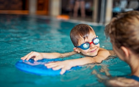 Young Boy in Pool with Mom and Wearing Goggles