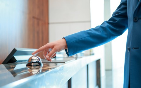Female Arm Wearing Blue Long Sleeve Touching Attendant Bell on Hotel Front Desk