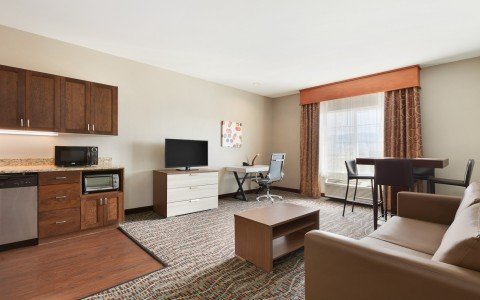 Guest Suite Living Area with Chair, Work Desk, Flat Screen TV and Kitchenette
