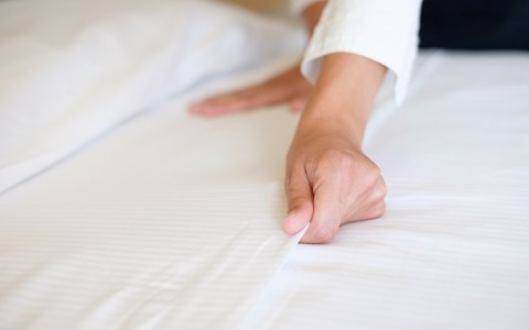 Maids Hands Straightening the White Sheets of a Bed