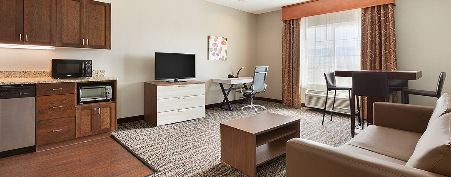 Queen Image Guest Suite Living Area with Chair, Work Desk, Flat Screen TV and Kitchenette
