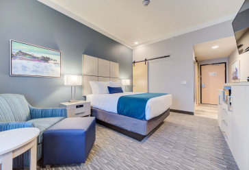Hotel room with queen bed, chair, ottoman, flatscreen television and dresser