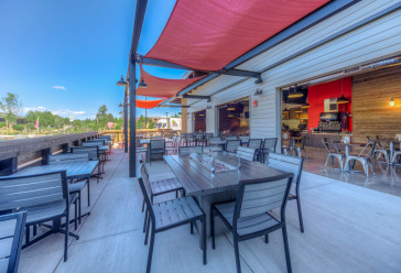 Zpizza and tap room outdoor seating area with dining tables and chairs
