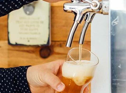 person pouring beer out of a tap