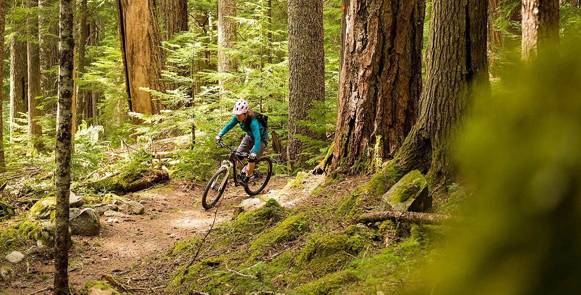 woman mountain biking on a trail