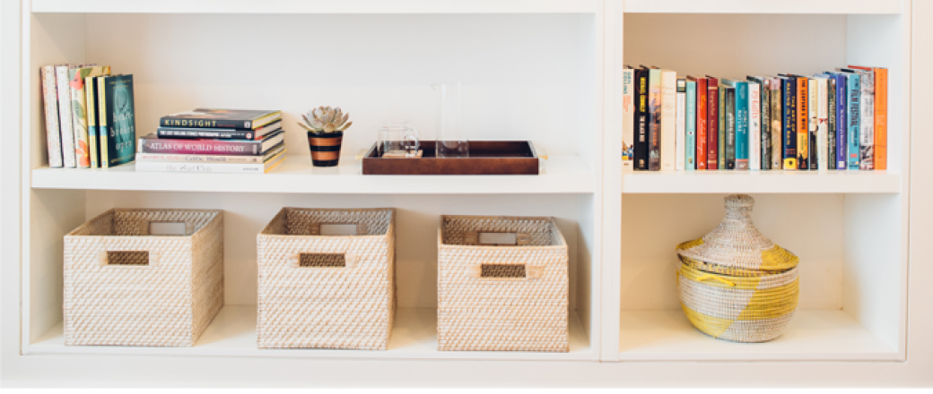 White shelving on wall with storage baskets, books & vase