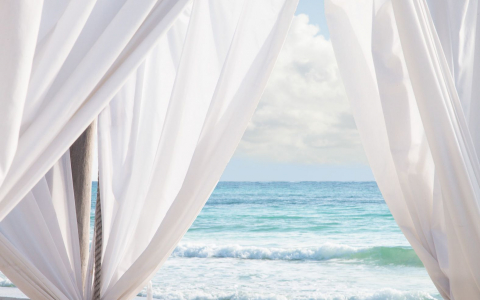 White sheer curtain fabric moving with the wind by the water