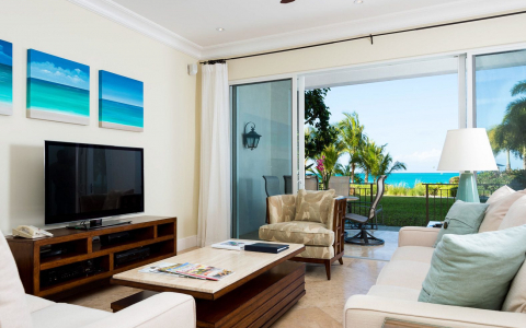In room living space with beige couches, wooden furniture, Tv & open balcony with ocean view