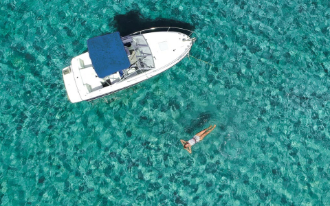 Aerial view of woman floating in water next to white boat