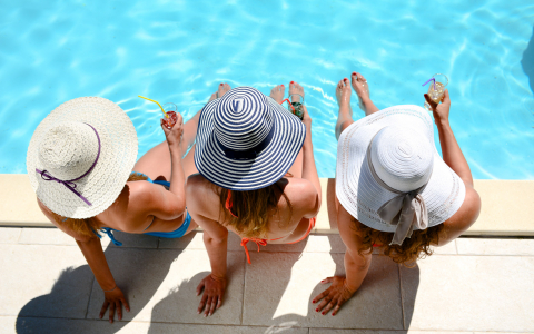 Three women with sun hats sitting at the edge of pool