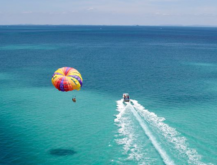 Aerial view of person parasailing over light blue waters