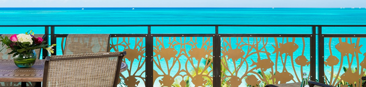 Outdoor terrace seating with gold fish fence design overlooking ocean