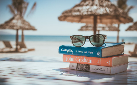 Books and sunglasses on a table by the sea