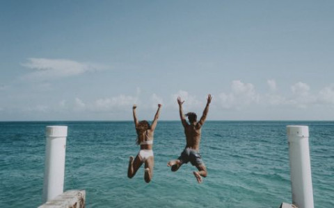 Couple jumping off dock